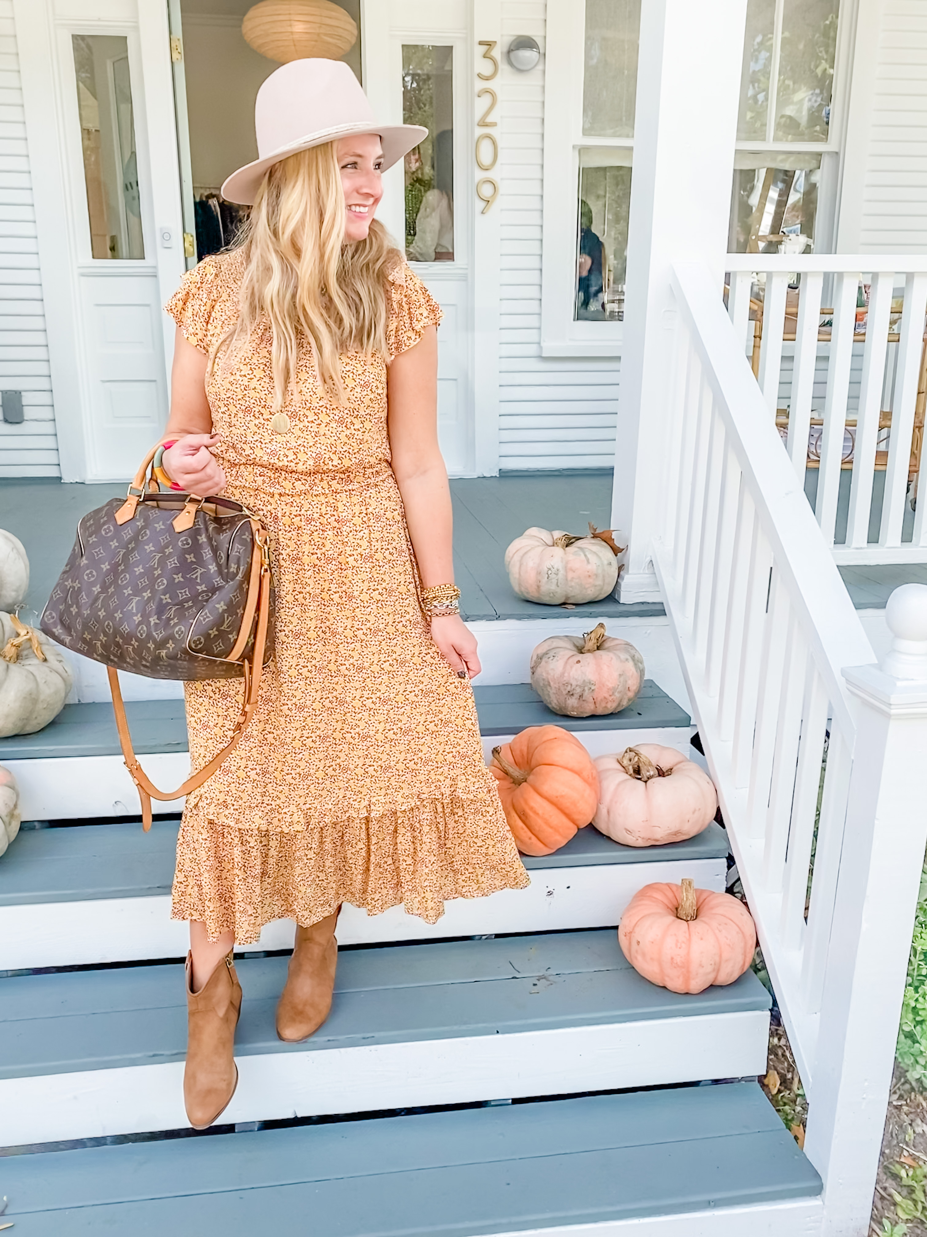 Cute Fall Outfits by popular Houston fashion blog, Fancy Ashley: image of a woman wearing a orange floral print ruffle hem maxi dress, felt hat, tan ankle boots and holding a Louis Vuitton bag.