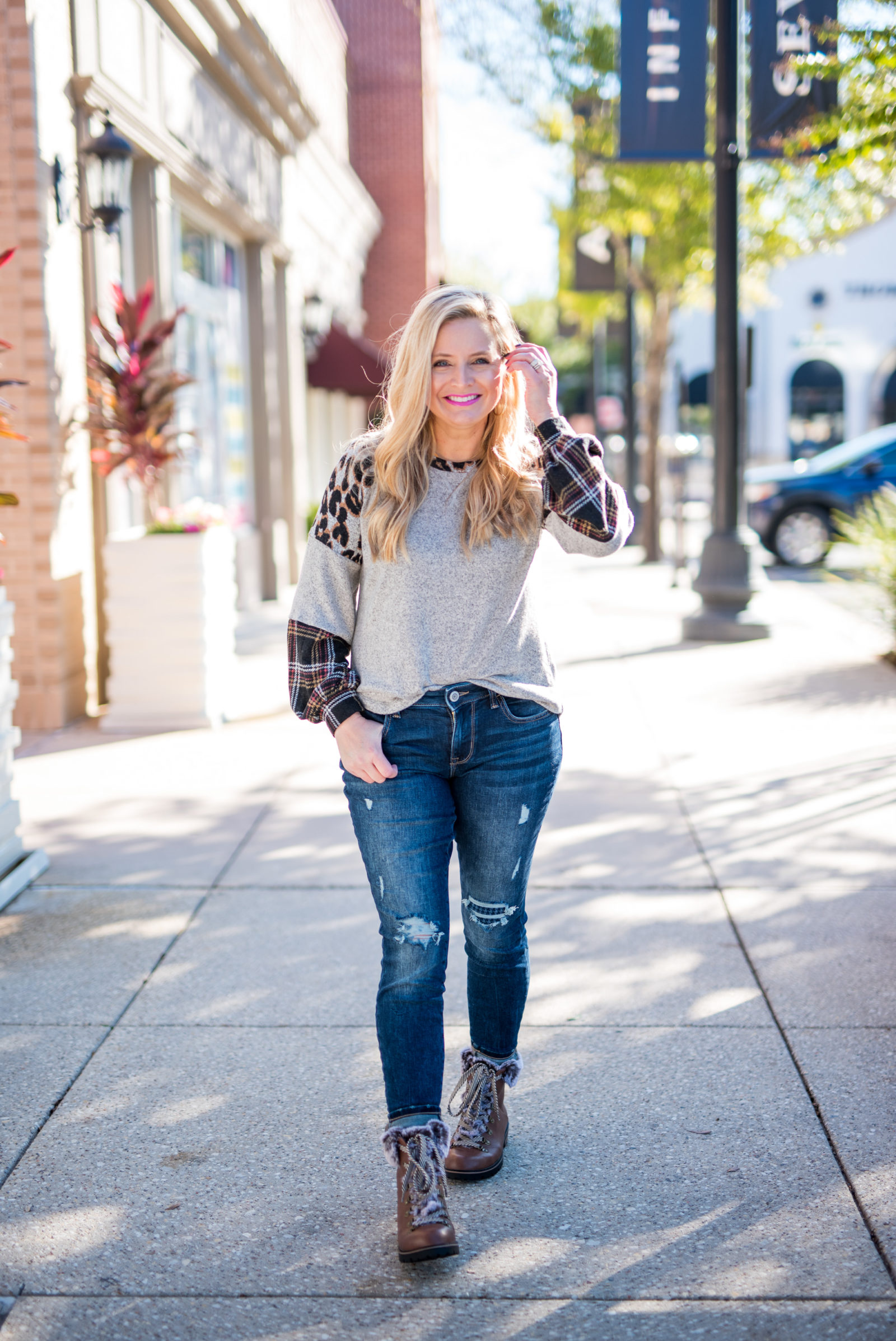Maurice's Clothing by popular Houston fashion blog, Fancy Ashley: image of a woman wearing a Maurice's 24/7 Leopard Plaid Colorblock Blouson Sleeve Baseball Tee, distressed denim, and brown fur trimmed combat boots.