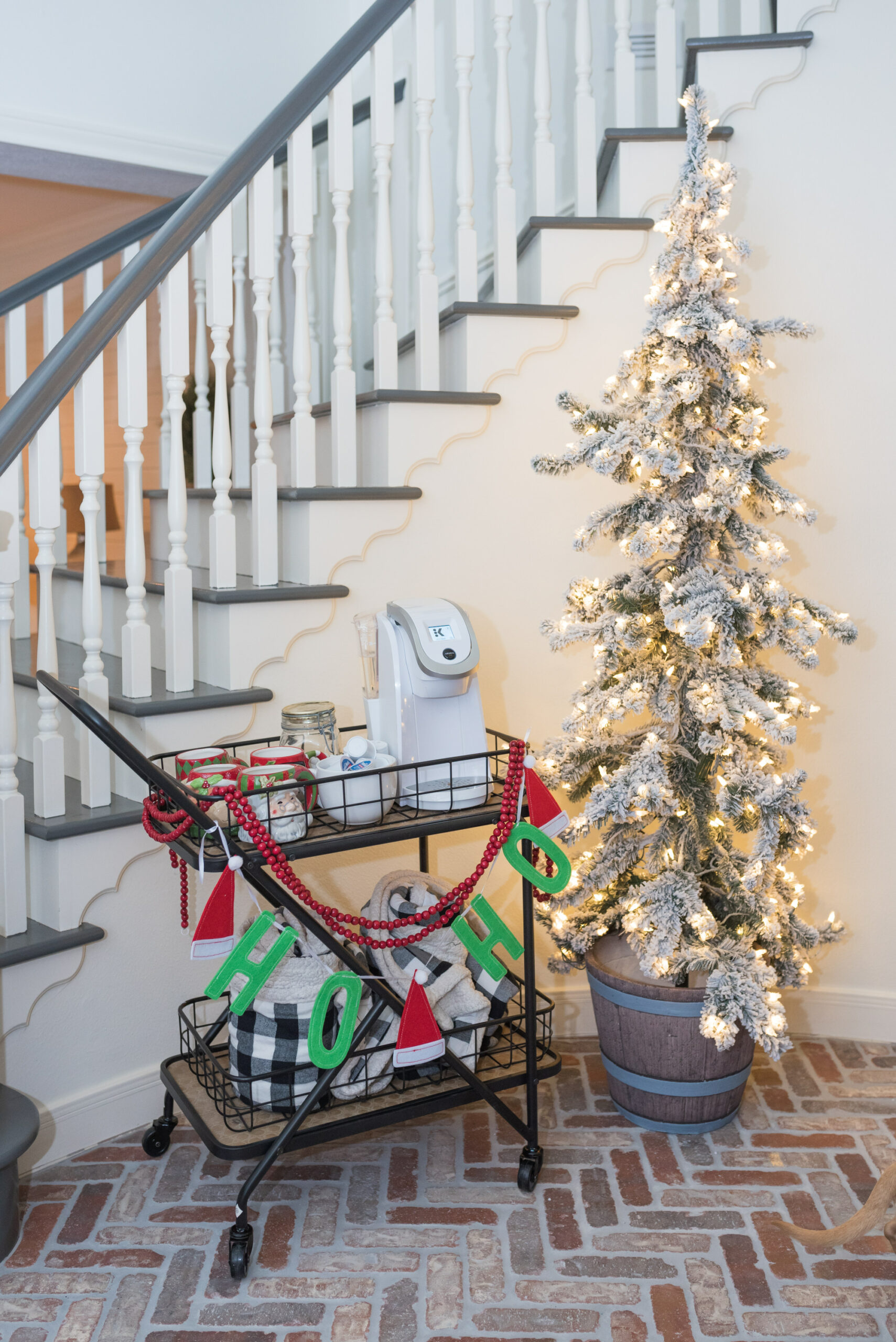 Hot Cocoa Bar by popular Houston lifestyle blog, Fancy Ashley: image of a black metal bar cart containing a Keurig, Santa mugs, Christmas garland, mini marshmallows, and coco pods.