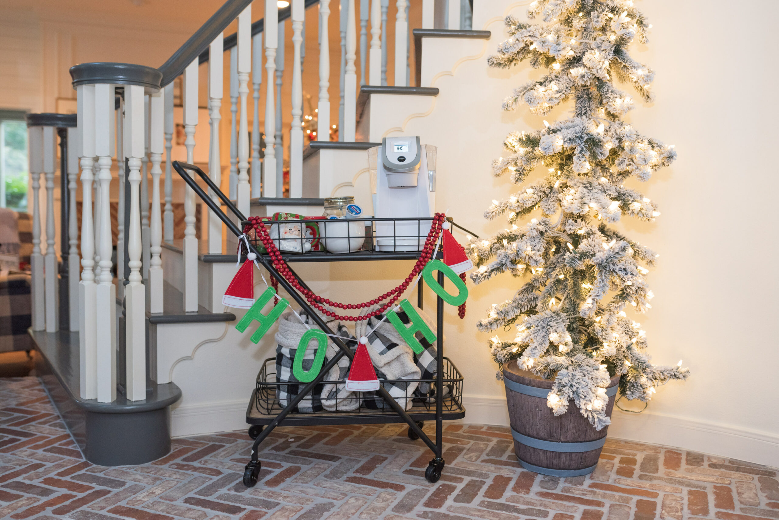 Hot Cocoa Bar by popular Houston lifestyle blog, Fancy Ashley: image of a black metal bar cart containing a Keurig, Christmas mugs, Christmas garland, mini marshmallows, and coco pods.