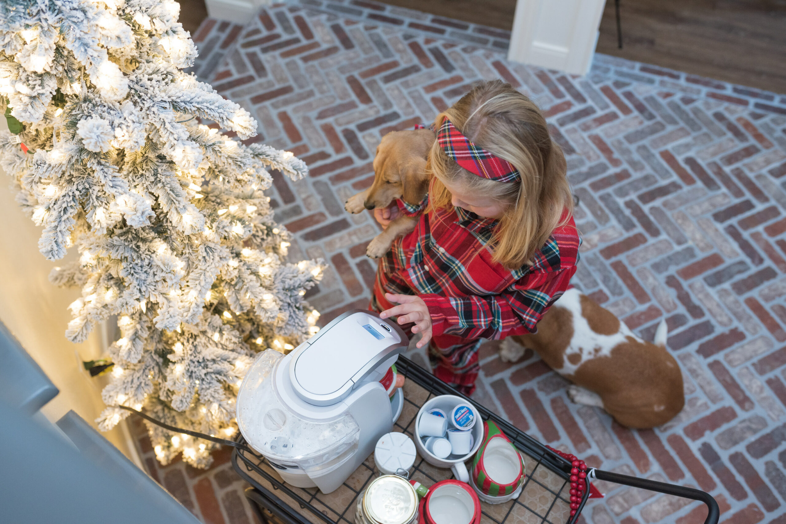 Hot Cocoa Bar by popular Houston lifestyle blog, Fancy Ashley: image of a little girl wearing plaid pajamas and holding her dog while standing next to a black metal bar cart containing a Keurig, Christmas mugs, Christmas garland, mini marshmallows, and coco pods.