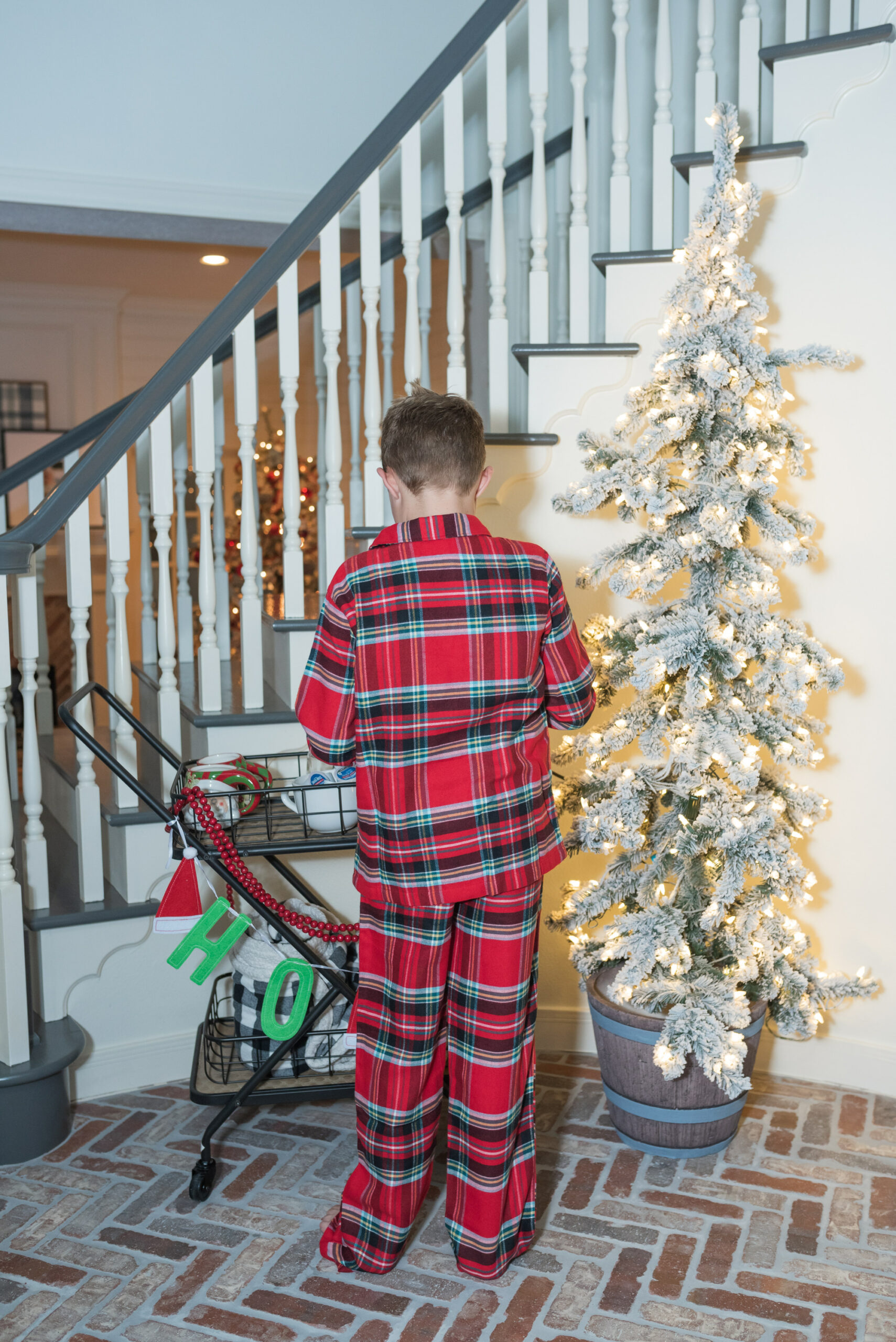 Hot Cocoa Bar by popular Houston lifestyle blog, Fancy Ashley: image of a young boy wearing plaid pajamas and standing next to a black metal bar cart containing a Keurig, Christmas mugs, Christmas garland, mini marshmallows, and coco pods.
