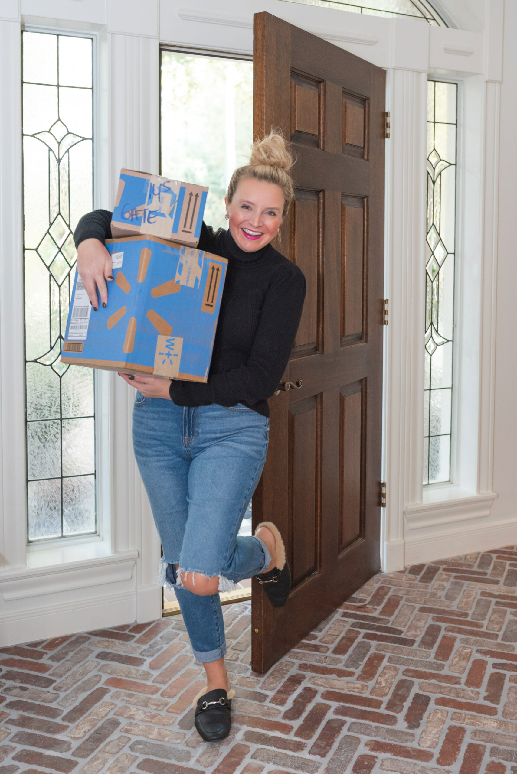 Walmart Gift Ideas by popular Houston life and style blog, Fancy Ashley: image of a woman coming through her front door while holding Walmart packages in her arms.