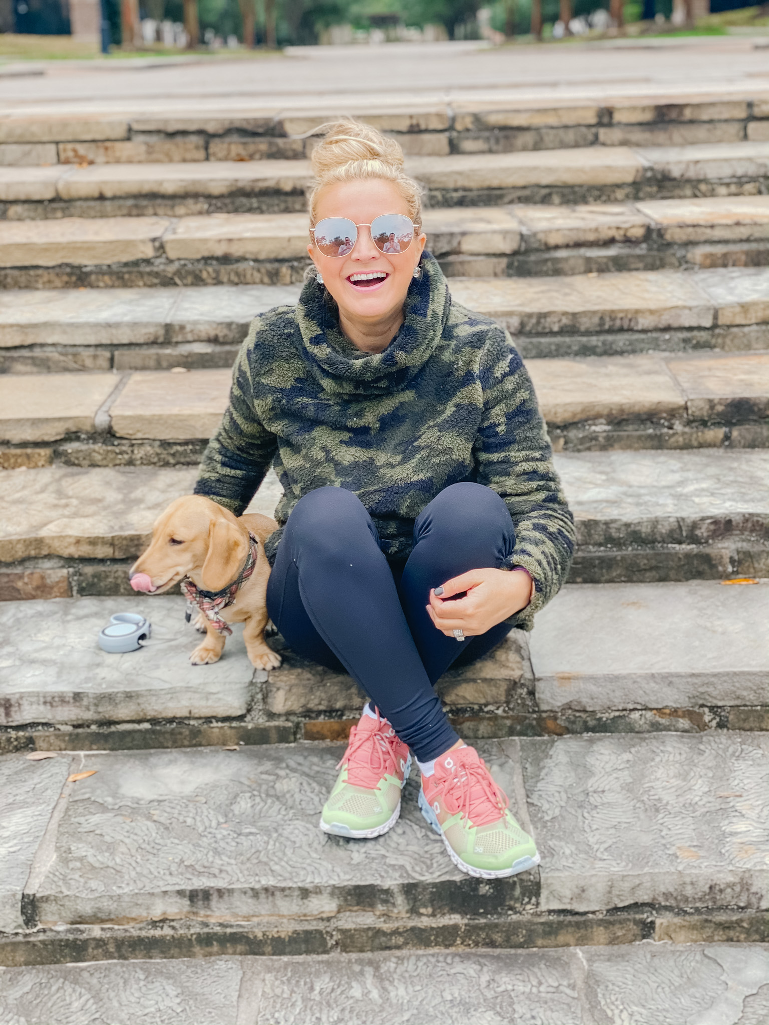 On Cloud Running Shoes by popular Houston fashion blog, Fancy Ashley: image of a woman sitting on some stone steps with her dog and wearing Shoes Cloudflow Running Shoes, Zella leggings, Zella camo fleece pullover, and Quay Australia sunglasses.