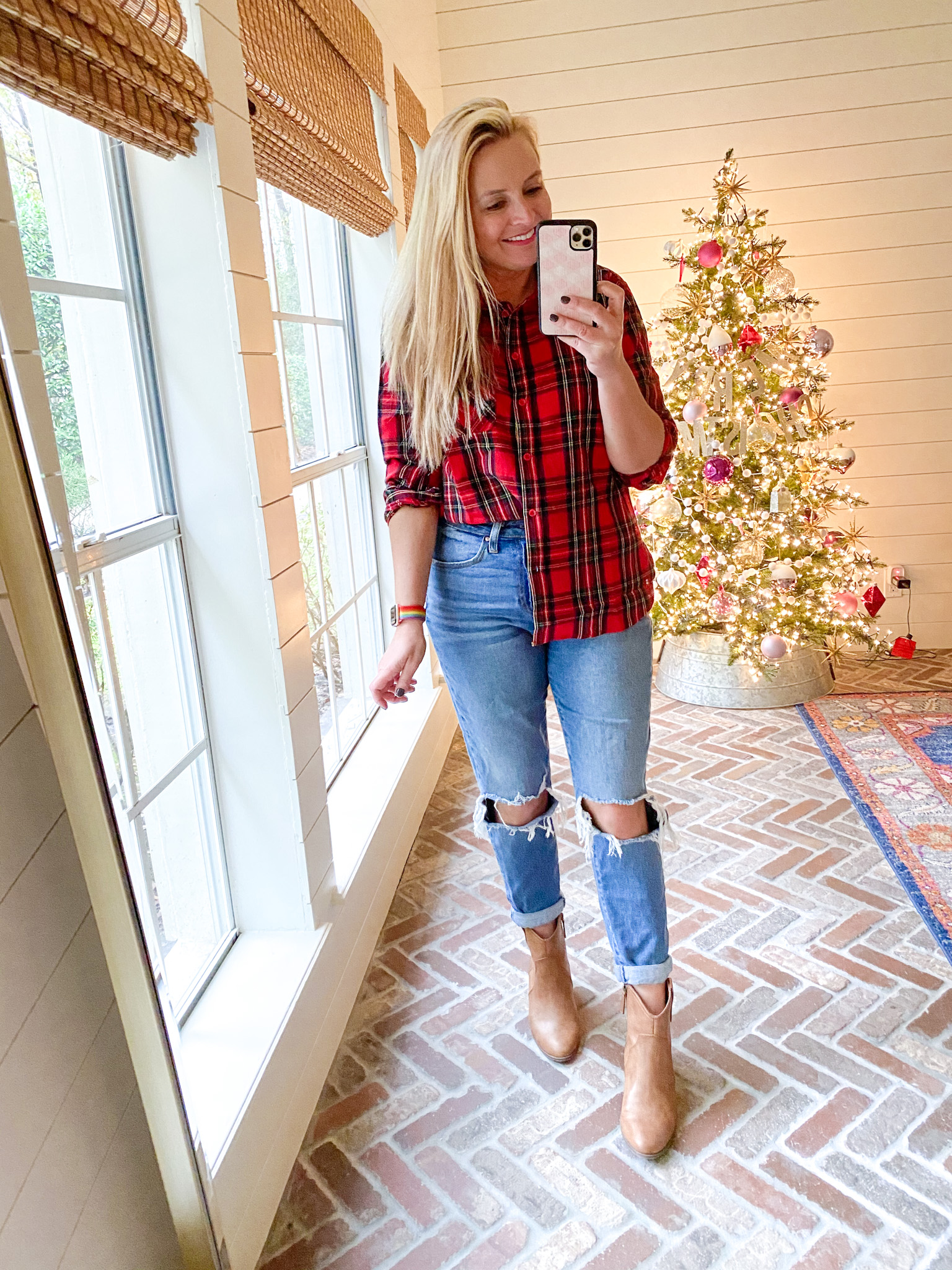 December Outfits by popular Houston fashion blog, Fancy Ashley: image of a woman standing in front of a Christmas tree decorated with pink, white and silver ornaments and wearing a red and green plaid button up top, distressed denim, and tan ankle boots.