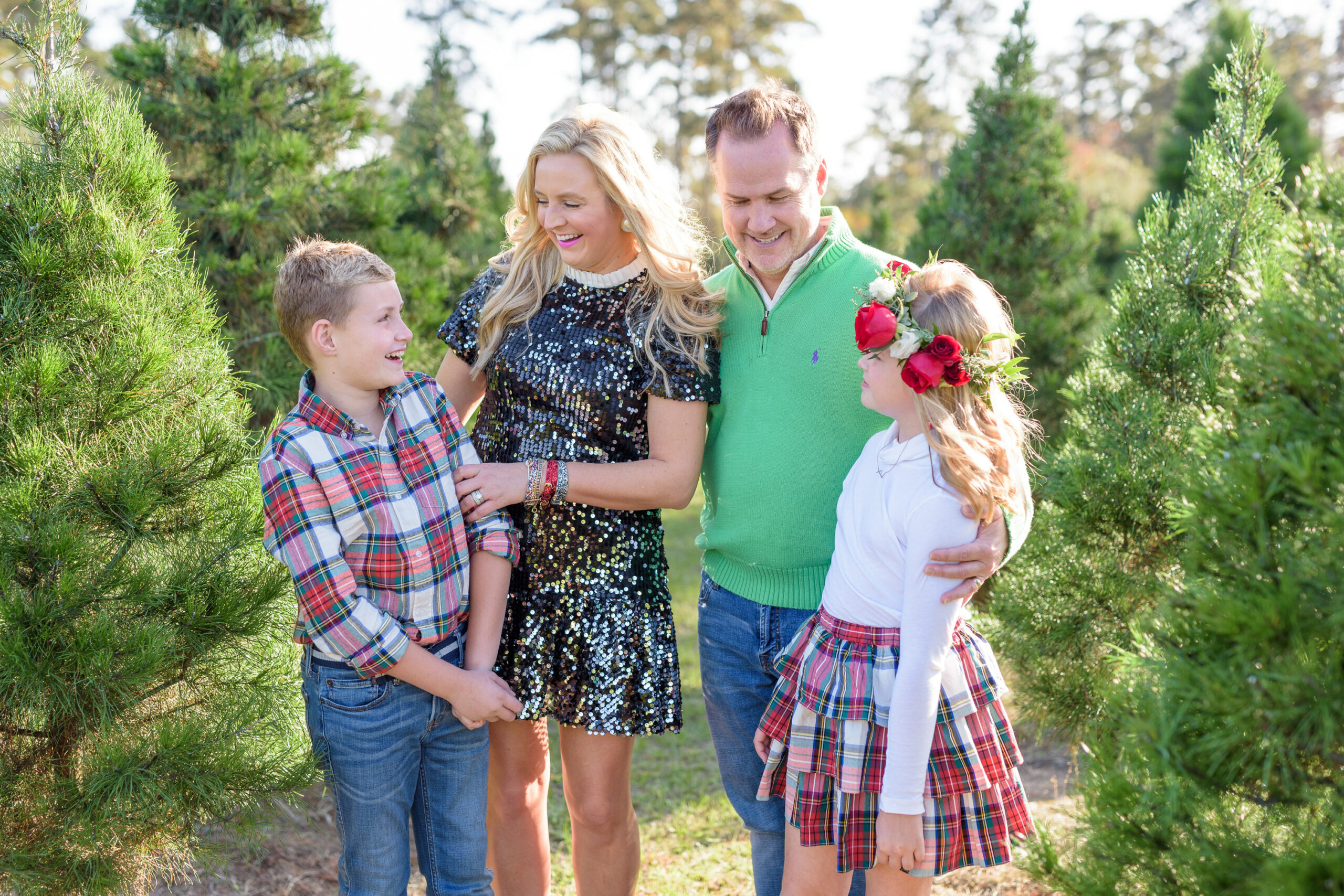 Christmas Tree Farm Photos by popular Houston lifestyle blog, Fancy Ashley: image of a family standing in a row of pine trees and wearing a black sequin dress, black suede ankle boots, plaid tier ruffle skirt, flower crown, plaid button up shirt, red loafers, and green pullover sweater.