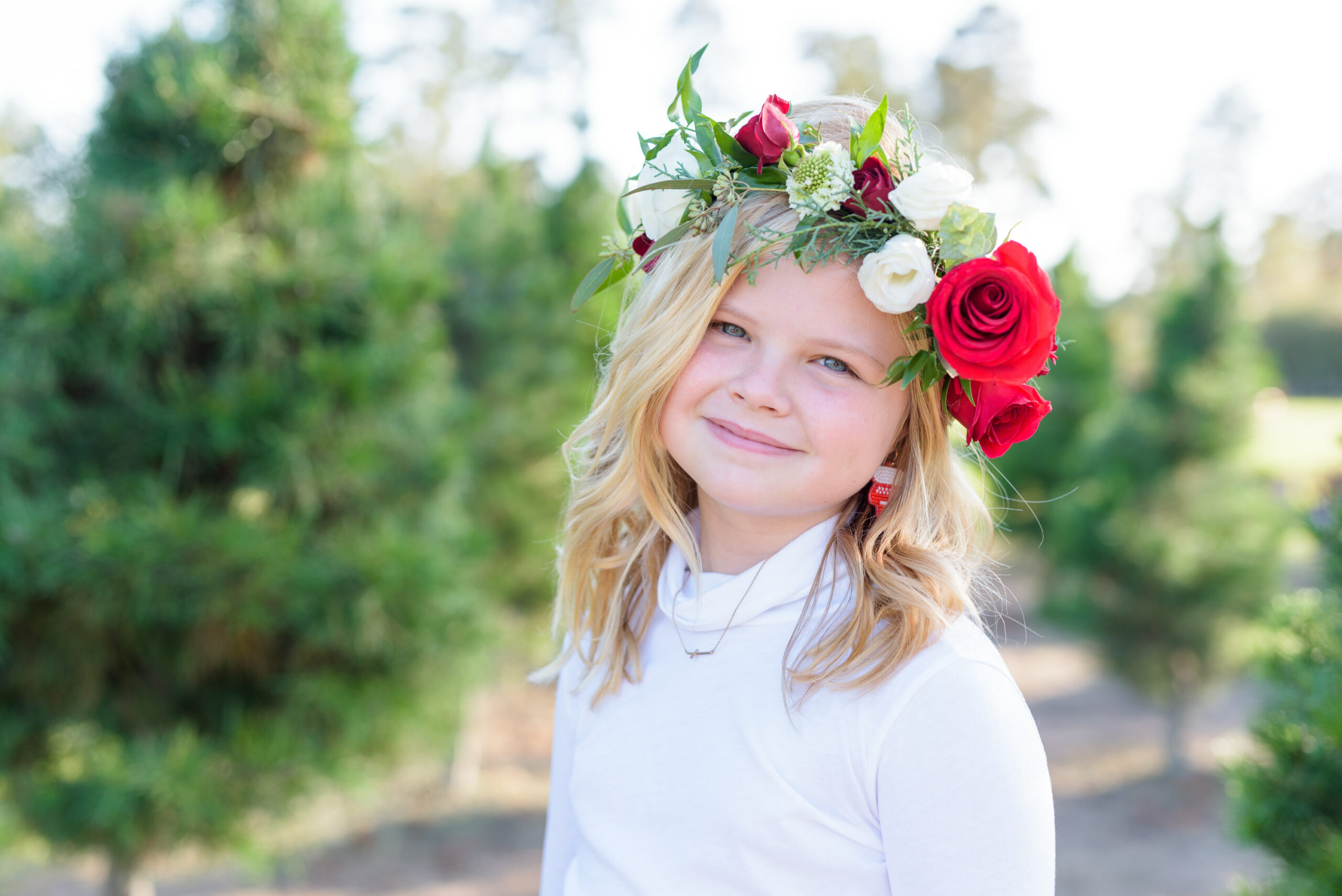 Christmas Tree Farm Photos by popular Houston lifestyle blog, Fancy Ashley: image of a girl standing in a row of pine trees and wearing a white long sleeve turtleneck, plaid tier ruffle skirt, flower crown