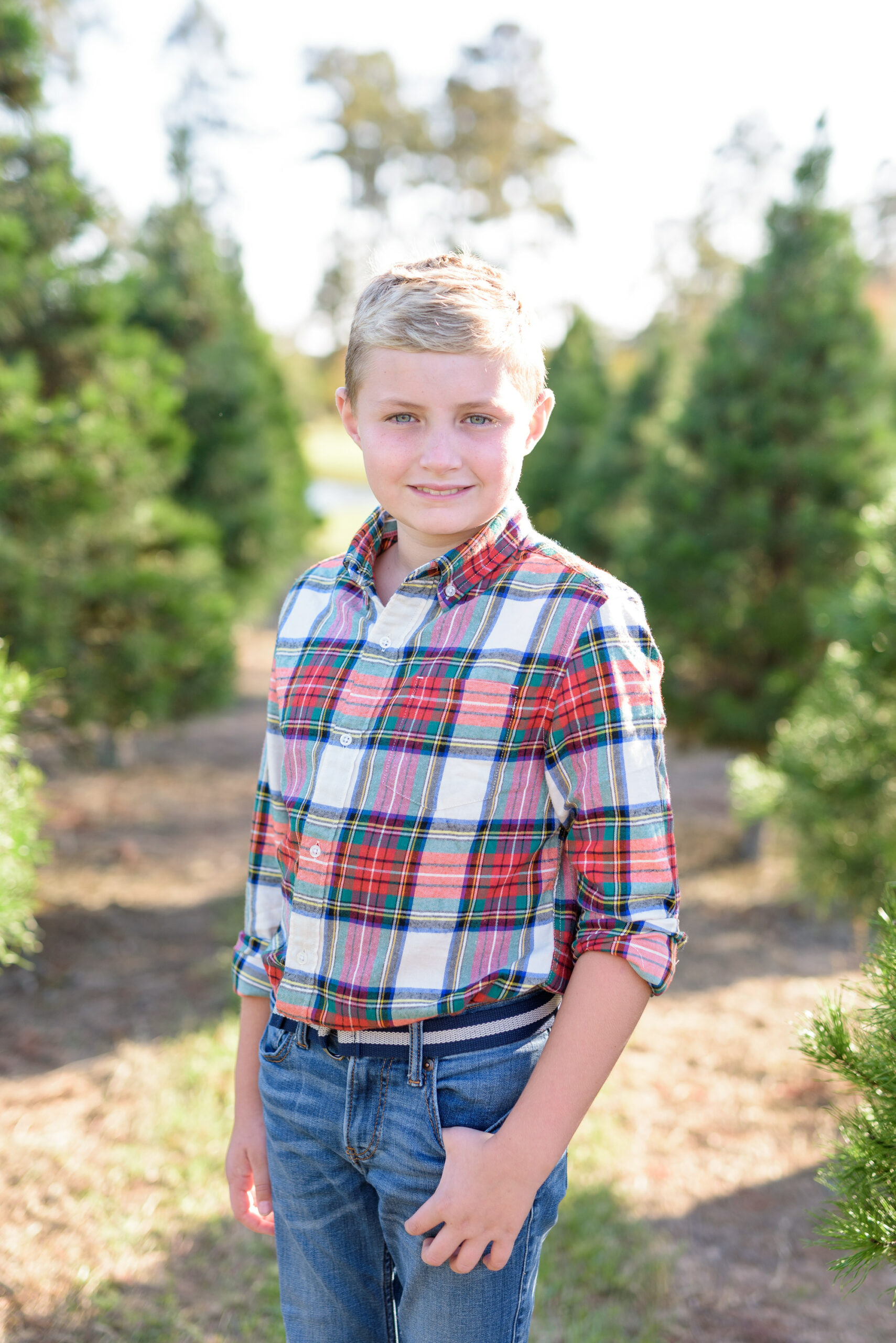 Christmas Tree Farm Photos by popular Houston lifestyle blog, Fancy Ashley: image of a boy standing in a row of pine trees and wearing a plaid button up shirt and jeans.