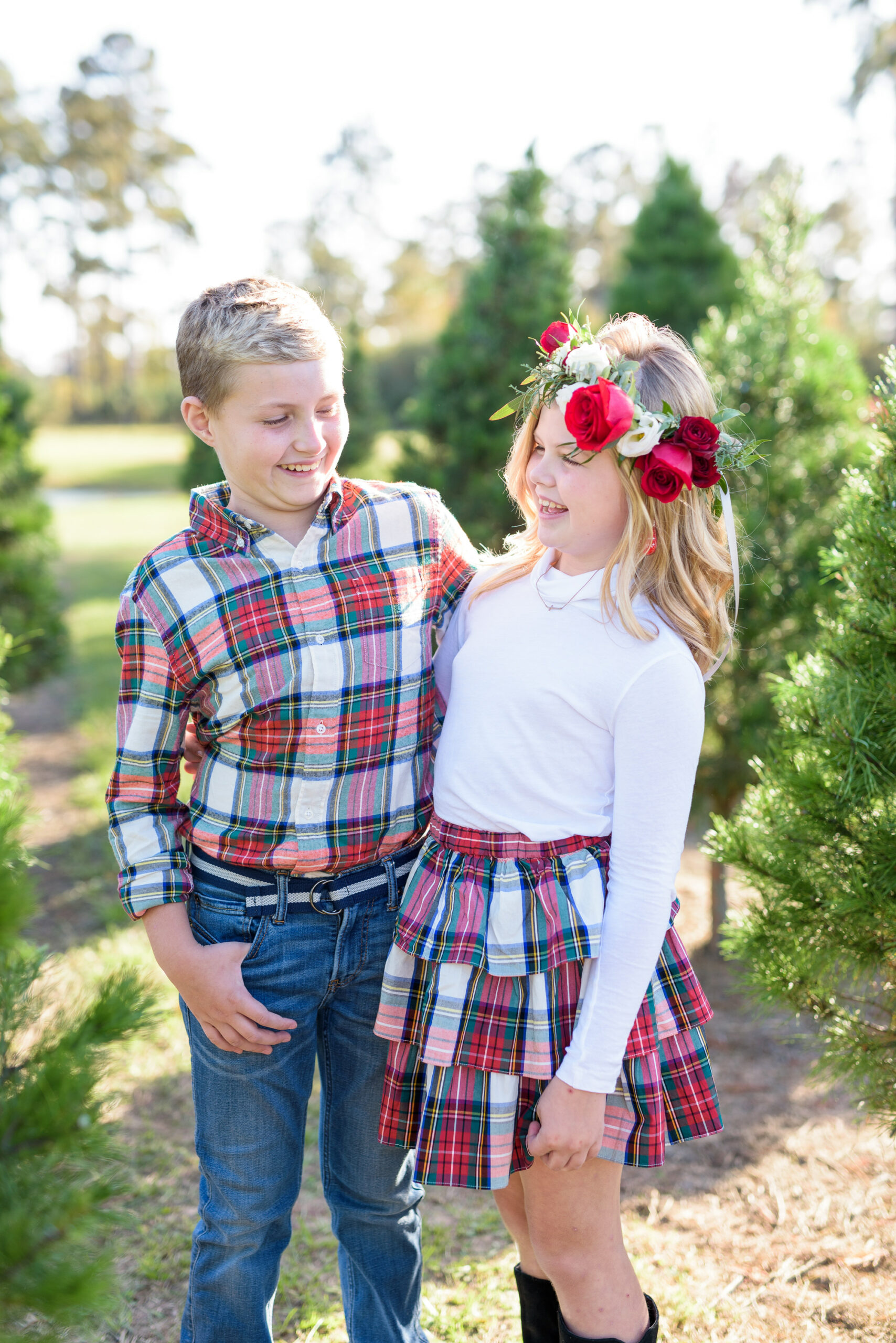 Christmas Tree Farm Photos by popular Houston lifestyle blog, Fancy Ashley: image of a young boy and girl standing together in a row of pine trees and wearing a white long sleeve turtleneck shirt, plaid tier ruffle skirt, flower crown, plaid button up shirt, and jeans.