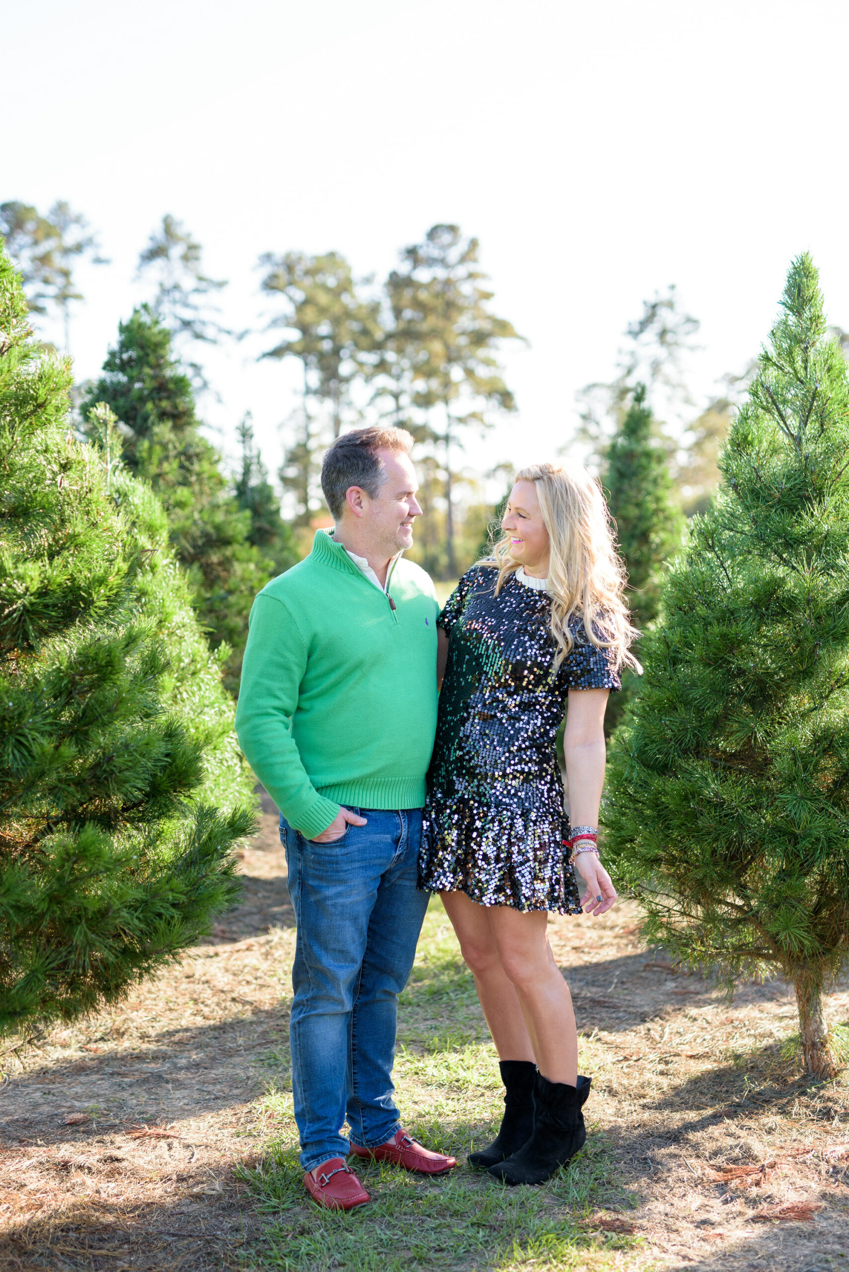 Christmas Tree Farm Photos by popular Houston lifestyle blog, Fancy Ashley: image of a husband and wife standing together in a row of pine trees and wearing a black sequin dress, black suede ankle boots, jeans, red loafers, and green pull over sweater.