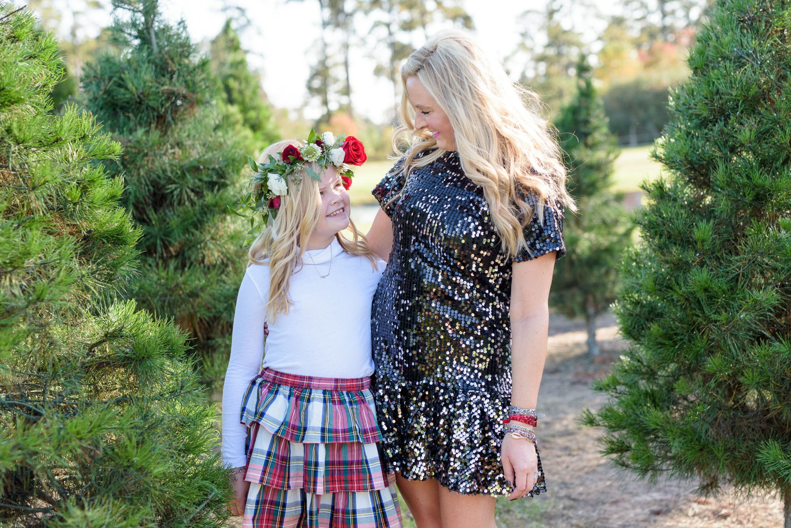 Christmas Tree Farm Photos by popular Houston lifestyle blog, Fancy Ashley: image of a mom and daughter standing together in a row of pine trees and wearing a black sequin dress, black suede ankle boots, plaid tier skirt, white long sleeve turtleneck shirt, and floral crown.