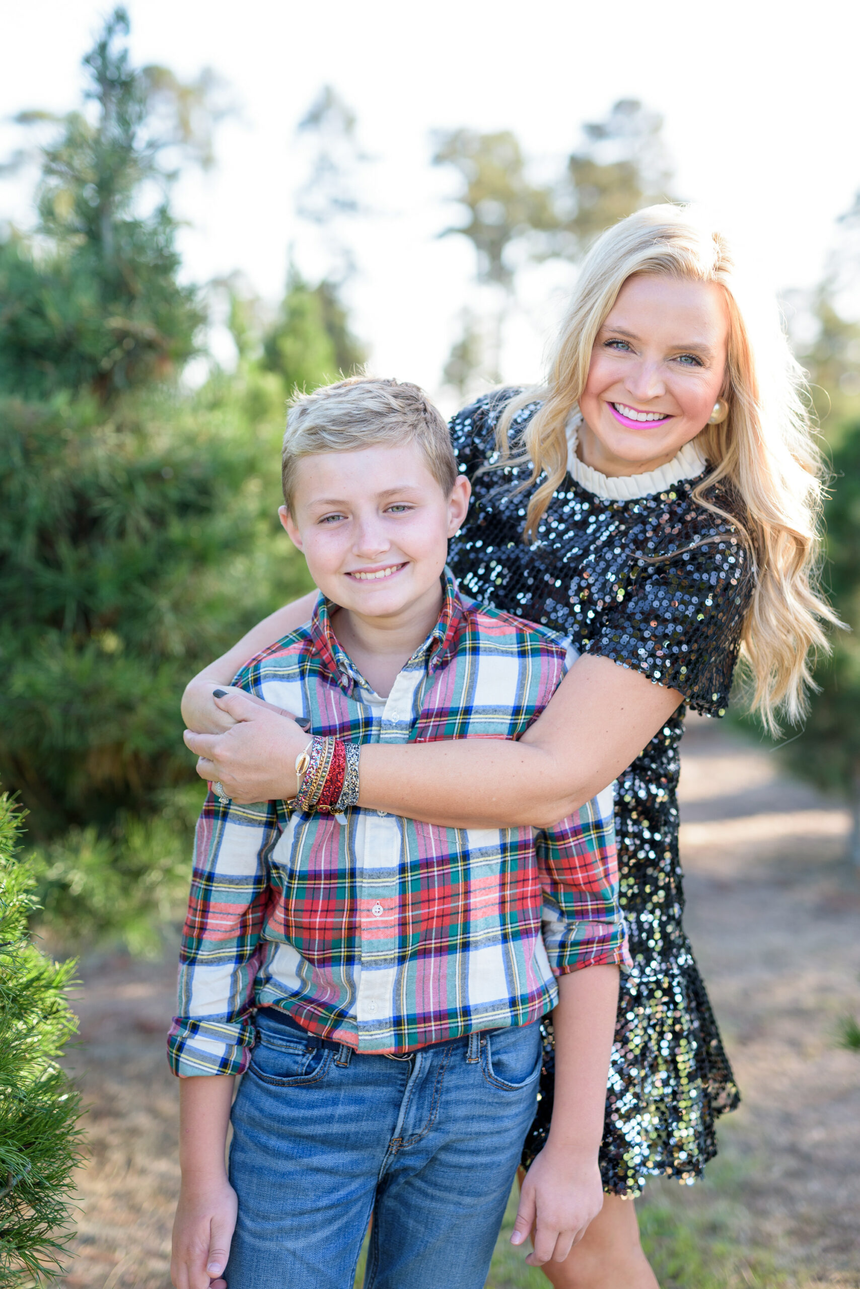 Christmas Tree Farm Photos by popular Houston lifestyle blog, Fancy Ashley: image of a mom and son standing together in a row of pine trees and wearing a black sequin dress, black suede ankle boots, plaid button up shirt, and jeans.