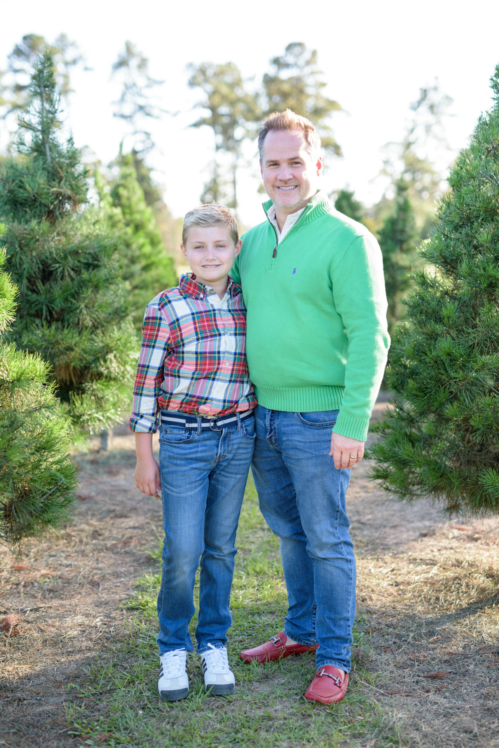 Christmas Tree Farm Photos by popular Houston lifestyle blog, Fancy Ashley: image of a dad and his daughter standing together in a row of pine trees and wearing a green pullover sweater, red loafers, plaid button up shirt, and jeans.