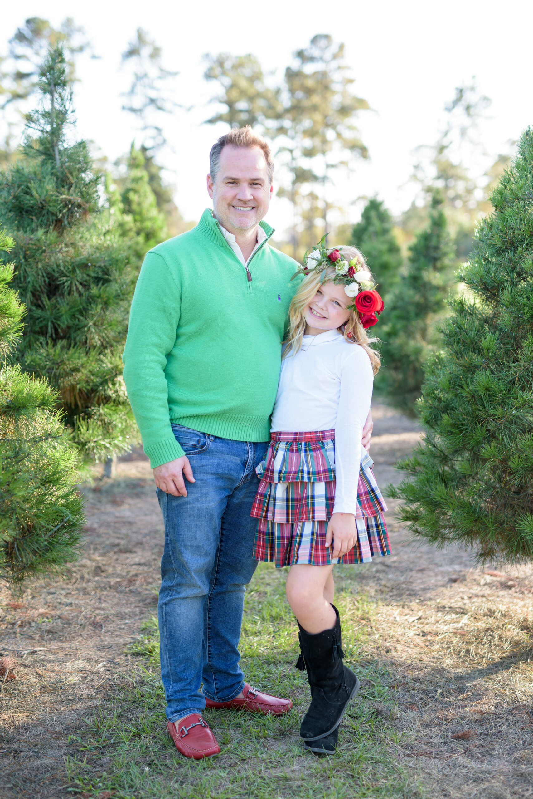Christmas Tree Farm Photos by popular Houston lifestyle blog, Fancy Ashley: image of a dad and his daughter standing together in a row of pine trees and wearing a green pullover sweater, white long sleeve turtleneck shirt, plaid ruffle tier skirt, floral crown and black suede boots.