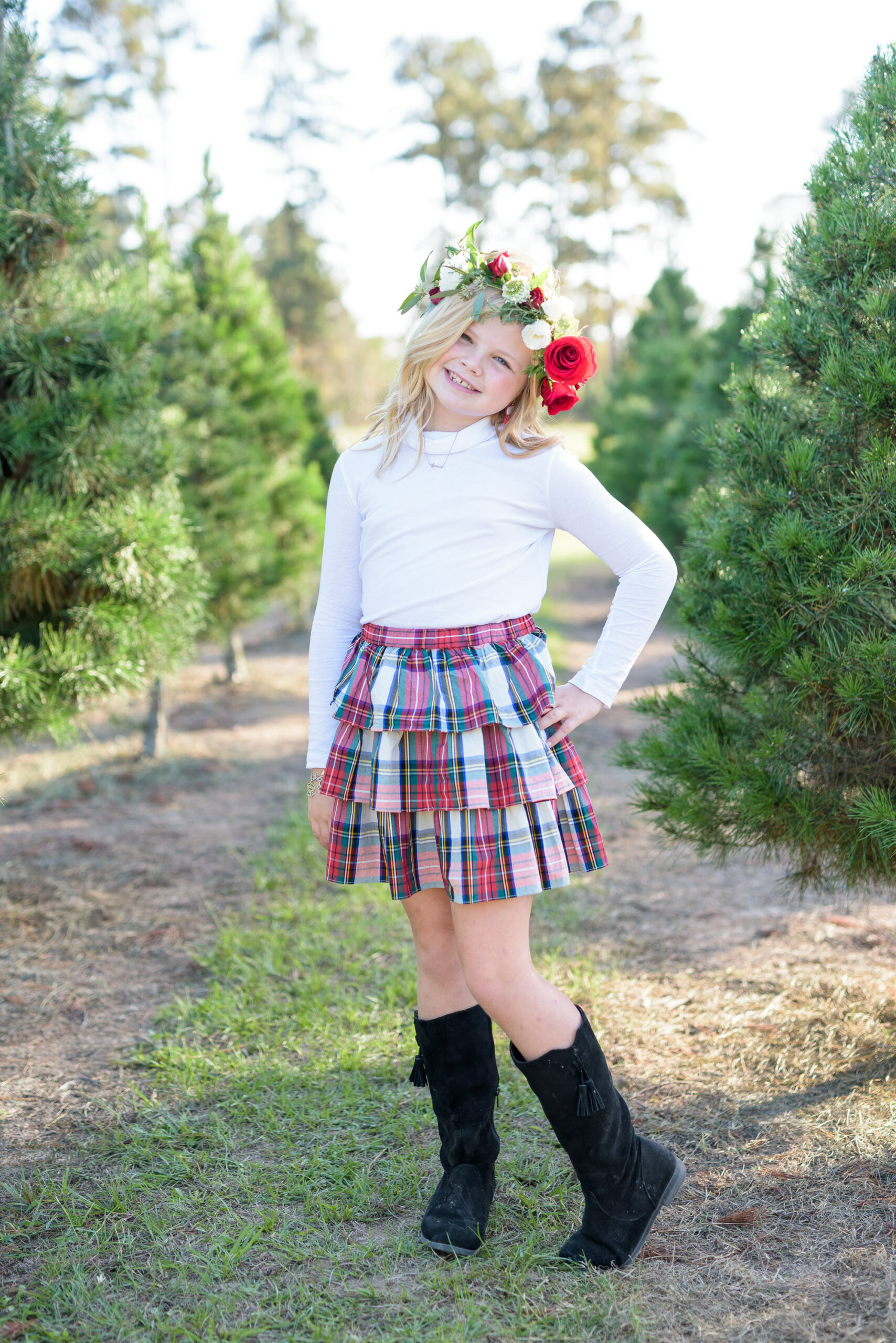 Christmas Tree Farm Photos by popular Houston lifestyle blog, Fancy Ashley: image of a girl standing in a row of pine trees and wearing a white long sleeve turtleneck shirt, plaid ruffle tier skirt, floral crown and black suede boots.