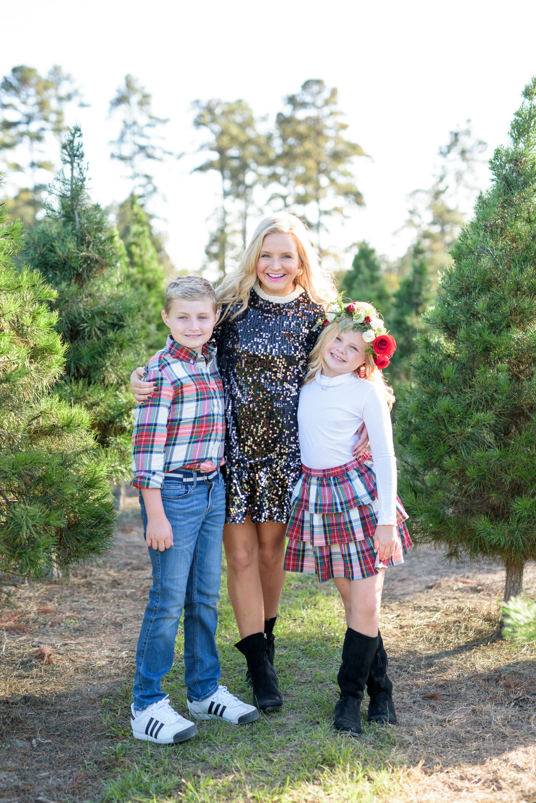 Christmas Tree Farm Photos by popular Houston lifestyle blog, Fancy Ashley: image of a mom and her two children standing together in a row of pine trees and wearing a black sequin dress, black suede ankle boots, plaid button up shirt, jeans, white long sleeve turtleneck shirt, plaid ruffle tier skirt, floral crown and black suede boots.