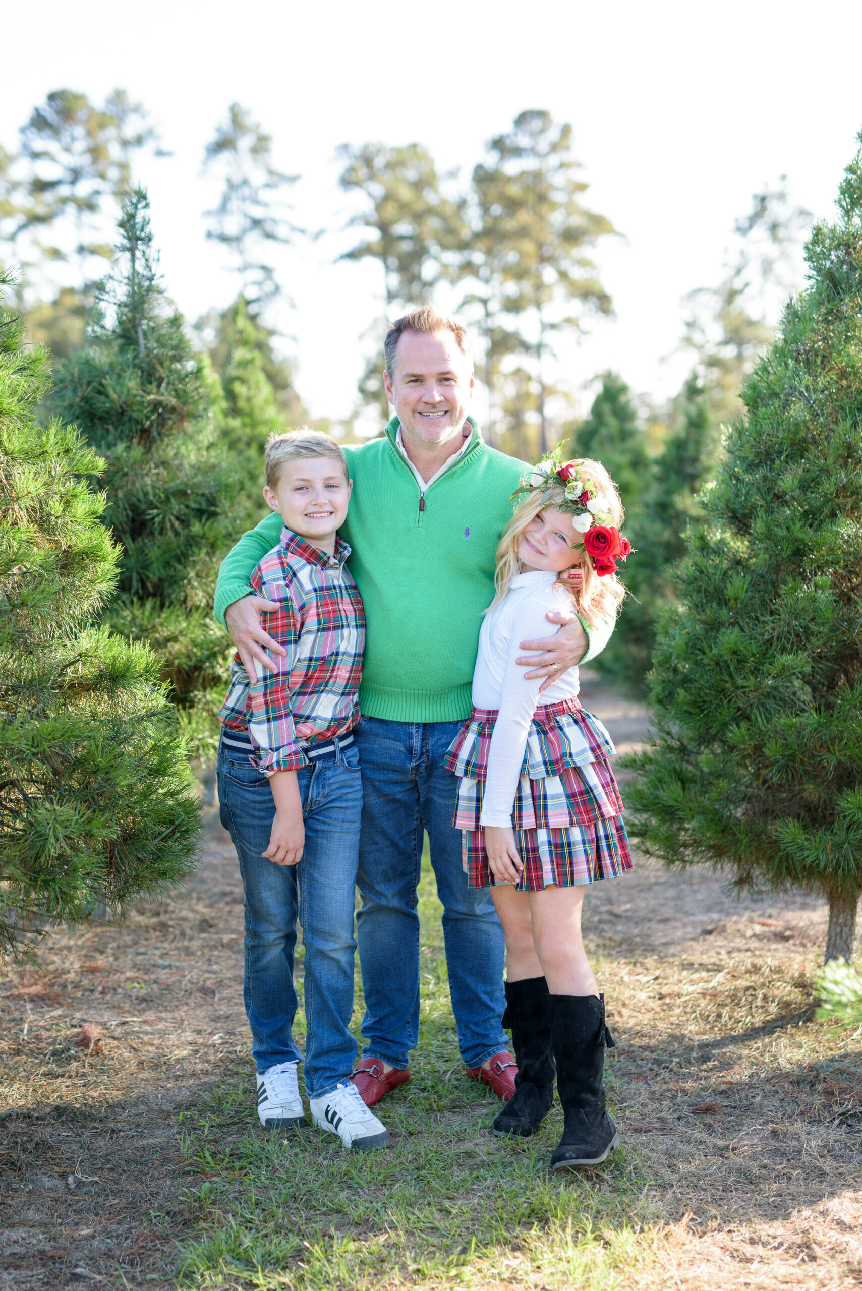 Christmas Tree Farm Photos by popular Houston lifestyle blog, Fancy Ashley: image of a dad and his two children standing together in a row of pine trees and wearing a green pullover sweater, red loafers, black suede boots, plaid button up shirt, jeans, white long sleeve turtleneck shirt, plaid ruffle tier skirt, floral crown and black suede boots.