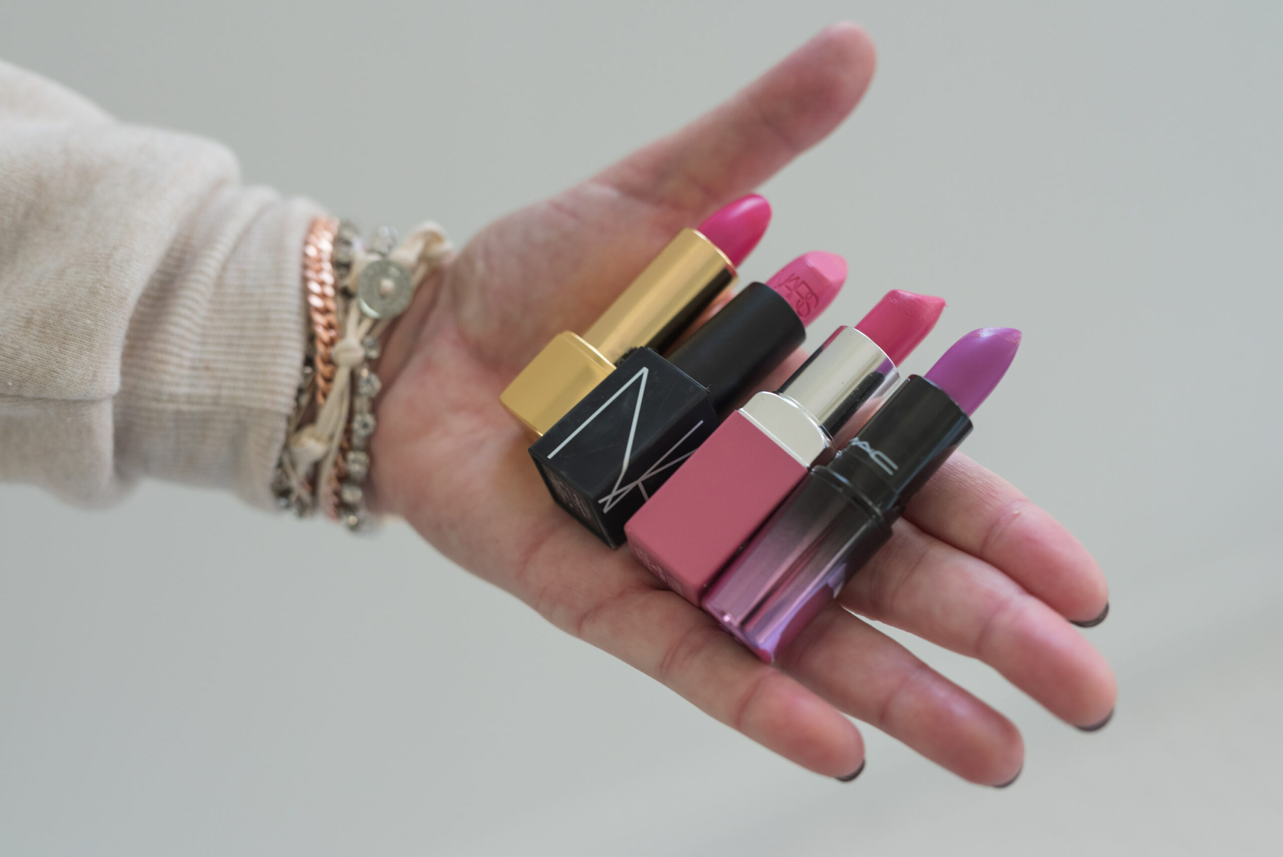 Nordstrom Beauty by popular Houston beauty blog, Fancy Ashley: image of a woman holding Nars lipstick, Mac lipstick, Clinique lipstick, and Let Them Eat Cake lipstick.