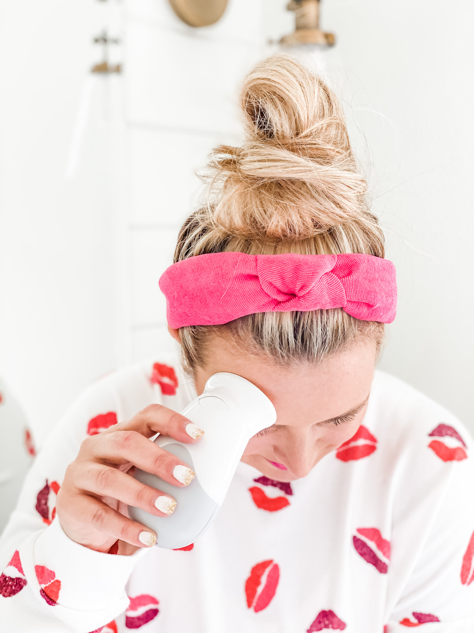 NuFace Trinity by popular Houston beauty blog, Fancy Ashley: image of a woman wearing a lip print pajama set and siting on her bathroom counter while using the NuFace Trinity facial toner.