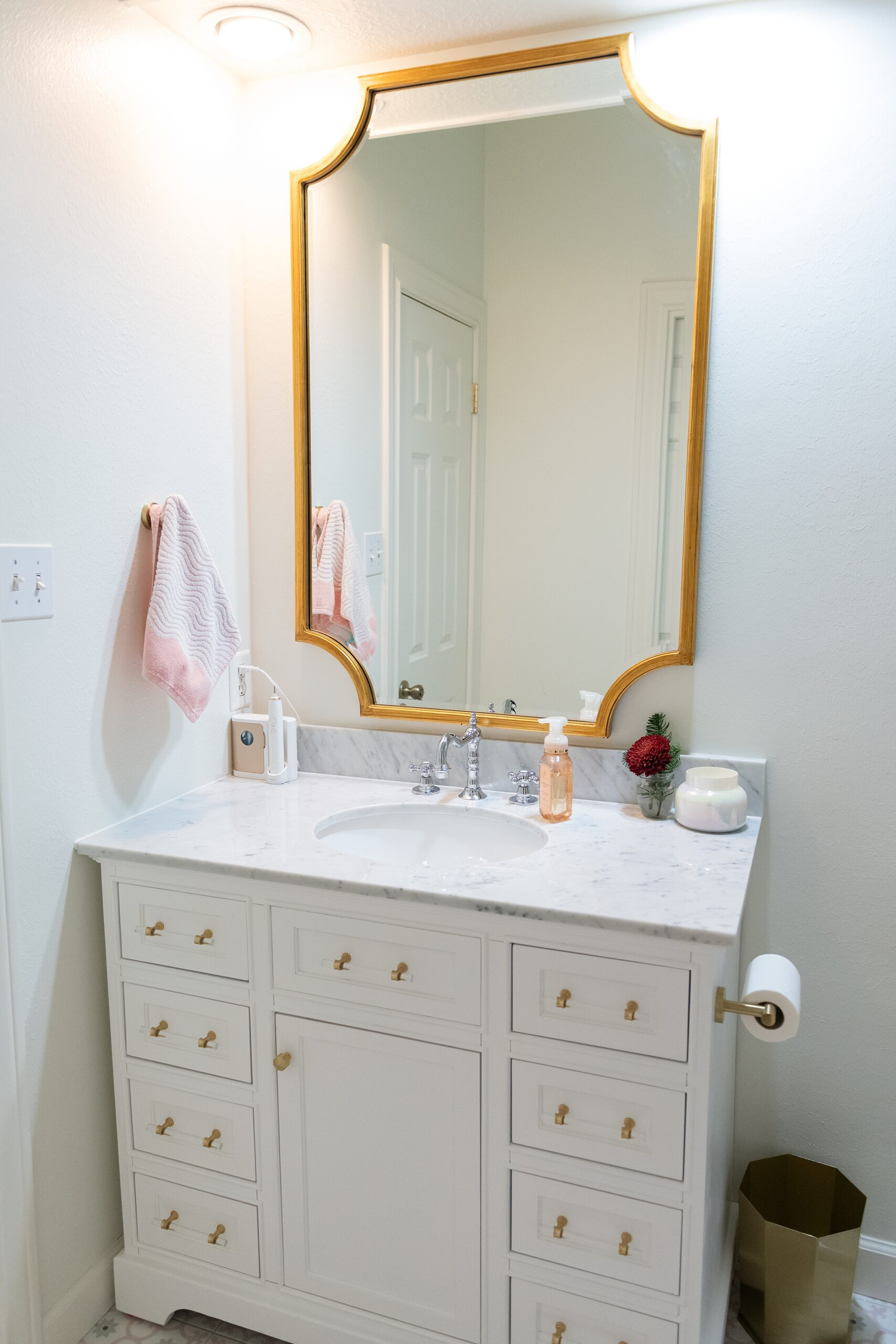 Girls Bathroom by popular Houston life and style blog, Fancy Ashley: image of a bathroom with pink and grey tile, white vanity with marble counter top and gold drawer pulls, and gold frame mirror.