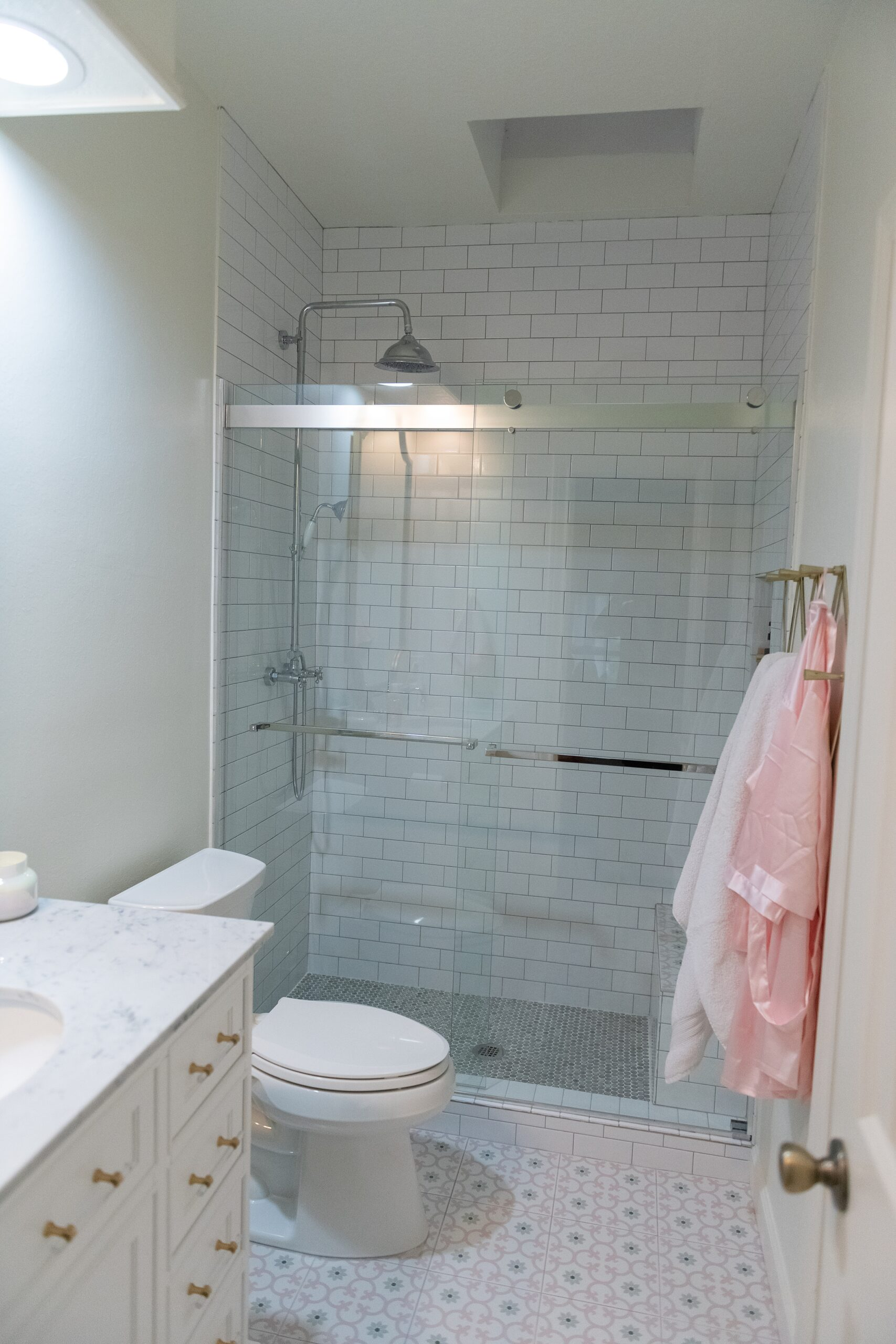 Girls Bathroom by popular Houston life and style blog, Fancy Ashley: image of a bathroom with pink and grey tile, white vanity with marble counter top and gold drawer pulls, gold towel hooks, and a walk in shower with subway tiles and grey penny tile flooring.