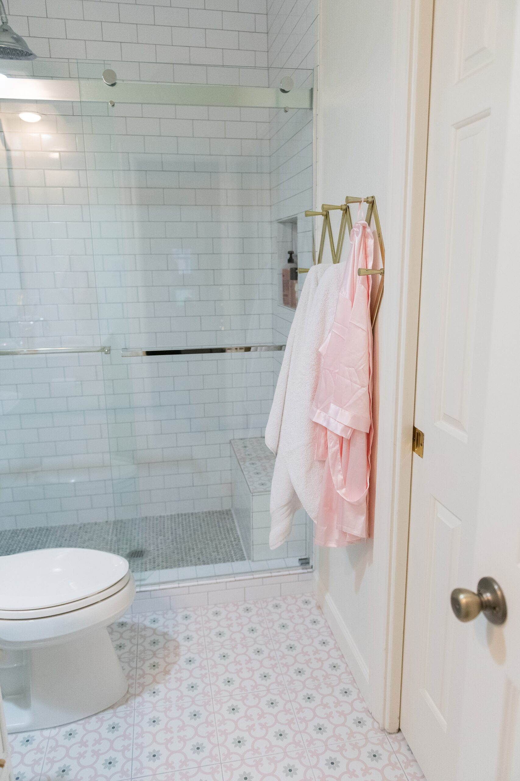 Girls Bathroom by popular Houston life and style blog, Fancy Ashley: image of a bathroom with a walk in shower that has white subway tile, pink and grey tiles, and grey penny tiles, pink and grey tile flooring a gold accordion wall hook with pink and white towels hanging from them.