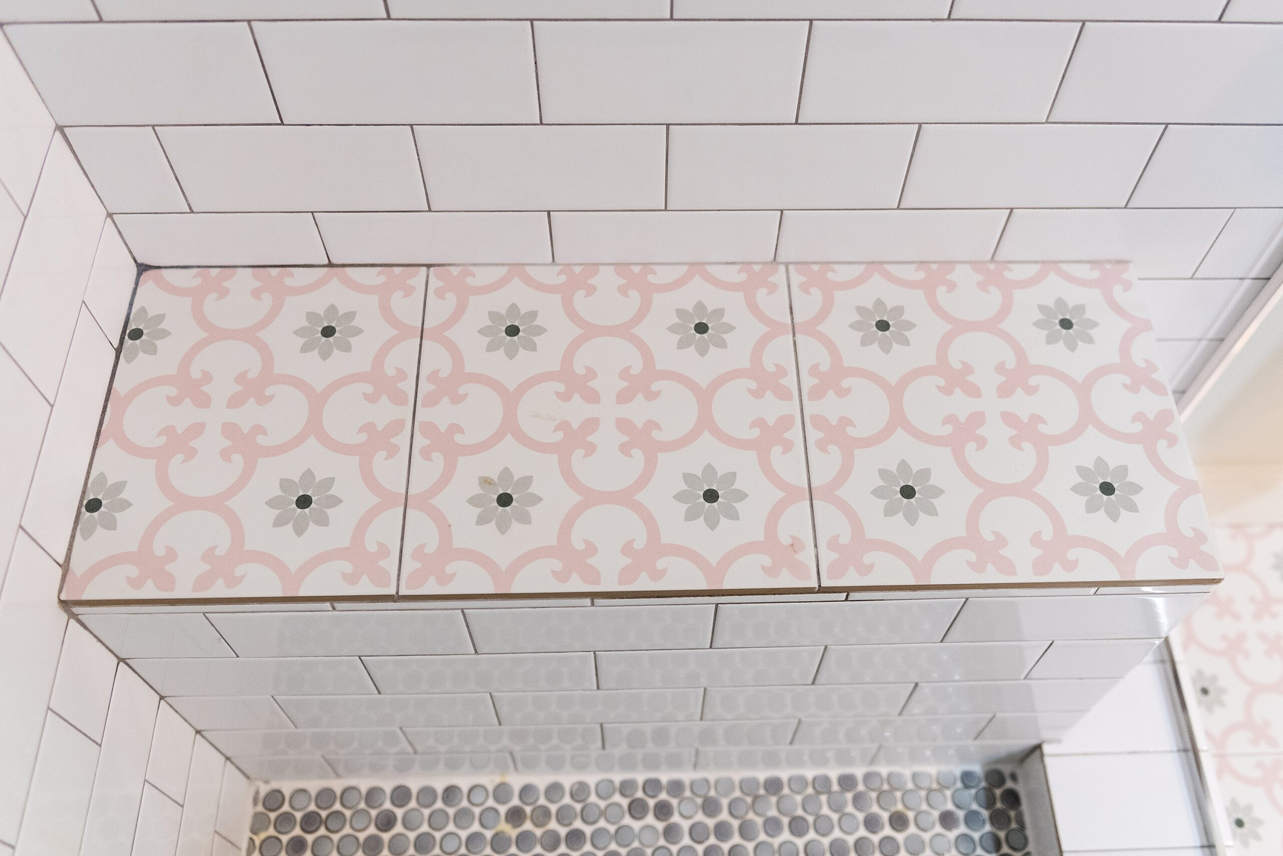 Girls Bathroom by popular Houston life and style blog, Fancy Ashley: image of a bathroom with a walk in shower that has white subway tile, pink and grey tiles, and grey penny tiles.