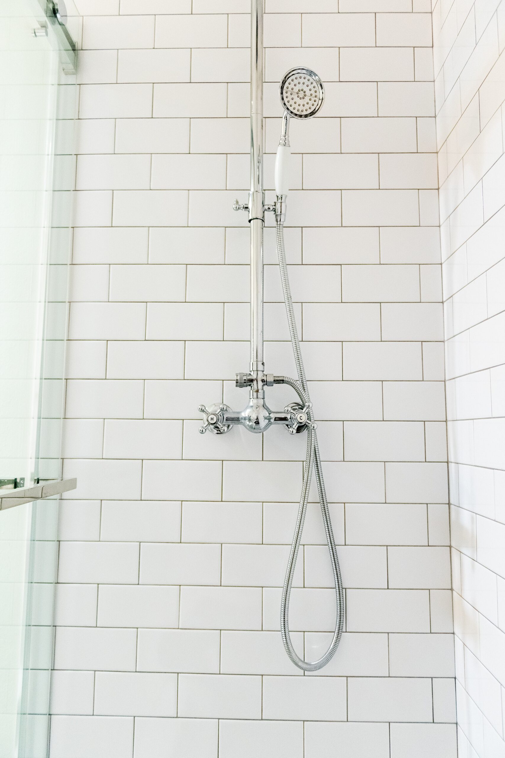 Girls Bathroom by popular Houston life and style blog, Fancy Ashley: image of a bathroom with a walk in shower that has white subway tile and hand held shower head.