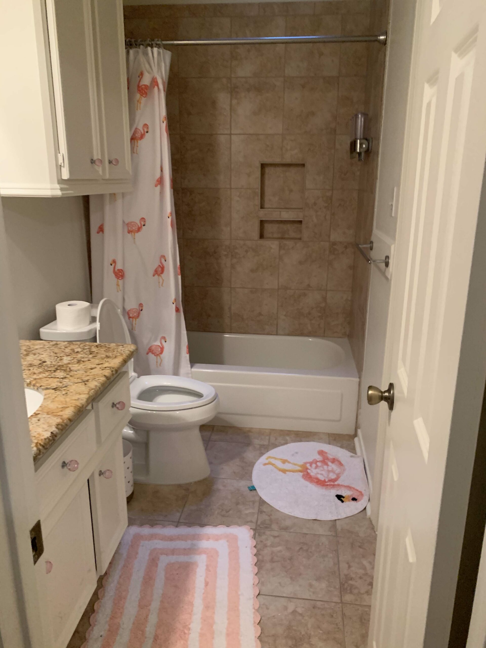 Girls Bathroom by popular Houston life and style blog, Fancy Ashley: image of a bathroom with brown tile, white cabinets, pink crystal drawer pulls, flamingo shower curtain, flamingo rug, and pink and white stripe scallop rug.